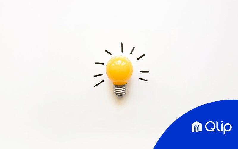 Bombilla amarilla encendida sobre fondo en blanco con el logo de Qlip simboliza la subida de la luz