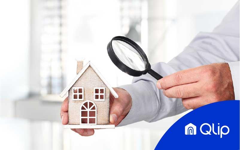 Persona sujetando casa de madera con una mano y una lupa con la otra como símbolo de seo local para inmobiliarias bajo el logo de Qlip