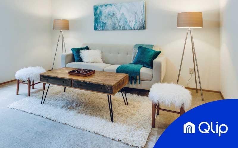 Home staging compuesto por un cuadro, sofá con almohadas, dos lámparas encendidas, mesita de salón, alfombra y dos taburetes blancos bajo el logo de Qlip