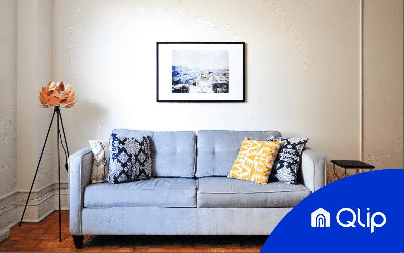 una fotografía inmobiliaria de calidad mostrando un salón con sofá, cuadro y lámpara | Qlip