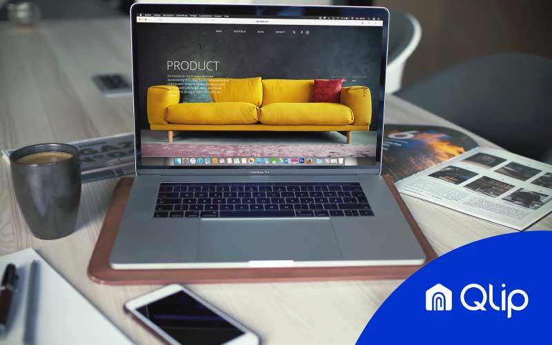 Ordenador portátil encima de la mesa con un sofá amarillo como fondo de pantalla y el logo de Qlip encima