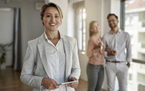 agente inmobiliario sonriendo a cámara tras un gran proceso de captación inmobiliaria después de seguir los consejos de Qlip, detrás de ella se encuentran dos clientes sonriendo a cámara